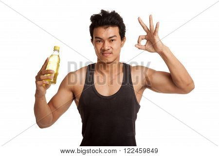 Muscular Asian man show OK with electrolyte drink  isolated on white background