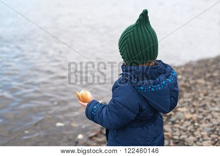 Child with a piece of bread on a river bank