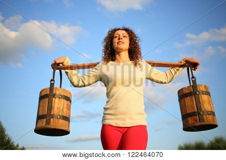 Portrait of a woman with a yoke and wooden pails against the blue sky