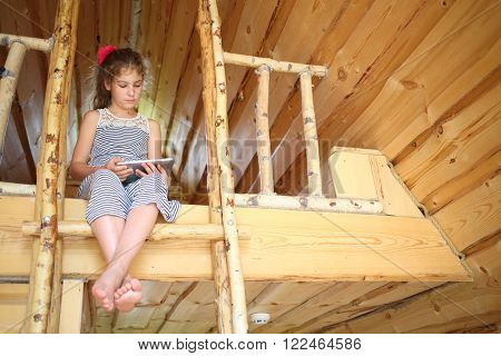 Barefoot girl with tablet computer sitting on the bunk in a wooden house