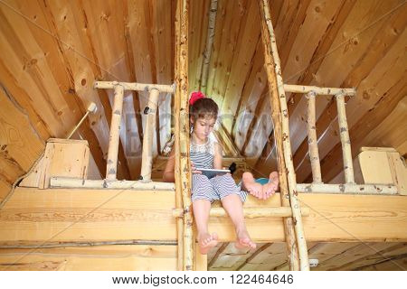 Girl with tablet computer in hands sitting on the bunk next to the other legs in a wooden house