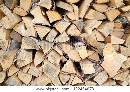 Neatly stacked birch firewood in woodpile, background poster