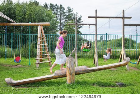 Mother with son and daughter swinging on a swing on a wooden playground