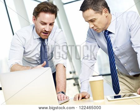 two caucasian business executives working together using laptop computer in office.