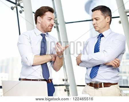 two caucasian business persons standing and chatting in office.
