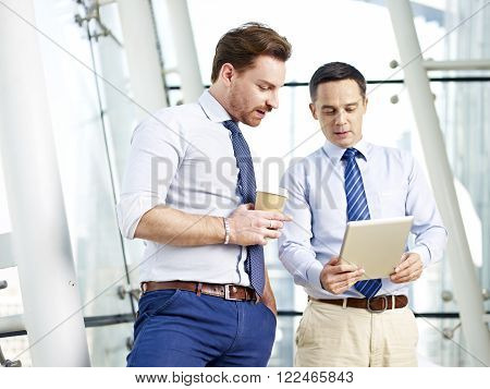 two caucasian business executives looking at and discussing data on tablet computer in office.