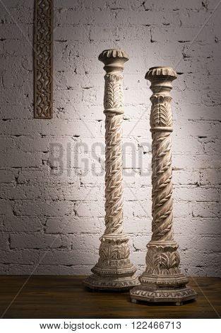 Composition of two white vintage wooden candlesticks on a background of wooden floor and white painted brick wall