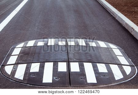 Road speed bump on the asphalt, transportation concept