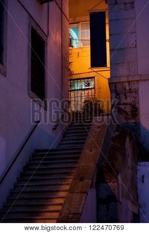 Light and shadows on a stone building and stairway in a quiet corner of old district Alfama in Lisbon, Portugal