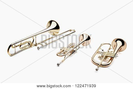 Set of brass musical instruments on a white background, include trumpet, trombone, flugelhorn an Trumpet, woodwind instruments.