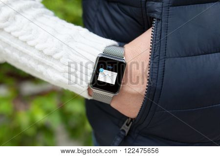 man hand in the pocket and smart watch with mail in the screen on the street