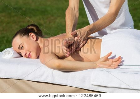 Man is rubbing back of young beautiful girl outside.
