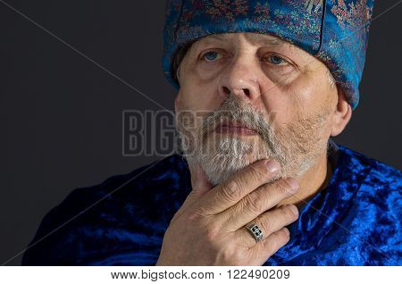 Nice portrait of meditating senior man in blue oriental clothes against dark background