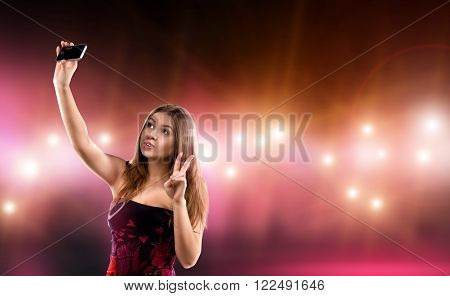 Sexy young woman in dress making selfie, surrounded by care and camera flash. Celebrity, model, star.