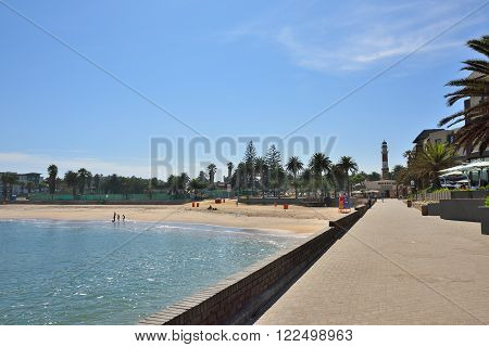 SWAKOPMUND NAMIBIA - FEB 1 2016: Public beach promenade and lighthouse in Swakopmund. Swakopmund was founded in 1892 by Captain Curt von Francois as the main harbour of German South West Africa