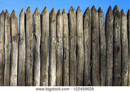 Palisade stockade pilings logs and blue sky. Abstract background old ancient.