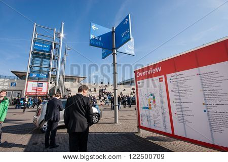 HANNOVER, GERMANY - MARCH 14, 2016: Attendees look at information board at CeBIT information technology trade show in Hannover, Germany on March 14, 2016.