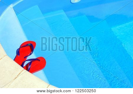 Flip-flops on on against blue water background.