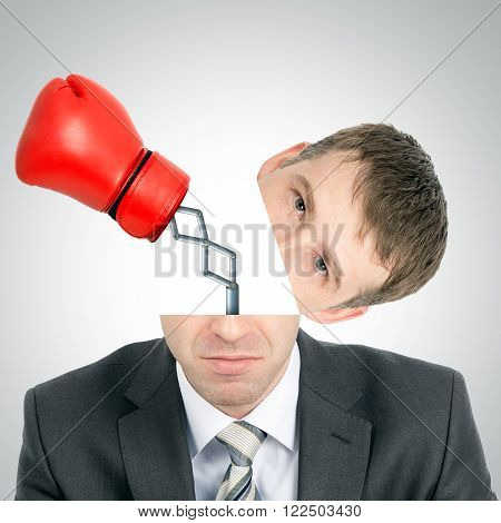 Boxing glove beating from businessmans head on grey background, front view