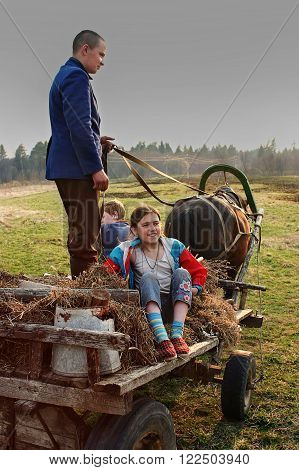Tver, Russia - May 4 2006: Young villagers go to the cart horse-drawn.