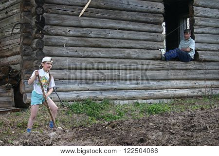Tver region Russia - May 7 2006: Tanya Girl 11 years old digs up the garden soil her brother Alexander 14 years old sitting in the doorway of the window of an abandoned log cabin.