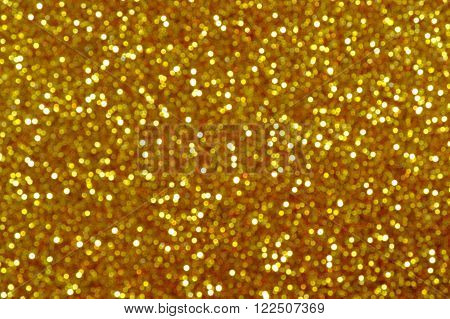 The photograph shows a yellow surface covered with glitter. Lens deliberately set beyond the point of focus to obtain a blur effect.
