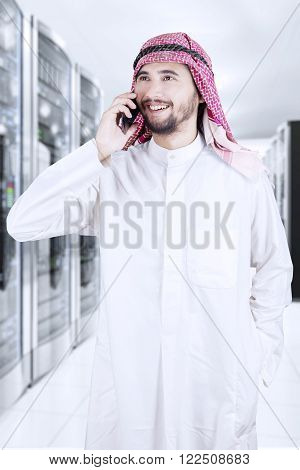 Portrait of arabian corporate worker talking on the phone while wearing traditional clothesPortrait of arabian corporate worker talking on the phone while wearing traditional clothes