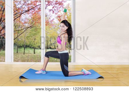 Picture of female athlete doing yoga exercise while wearing sportswear on the mat at home