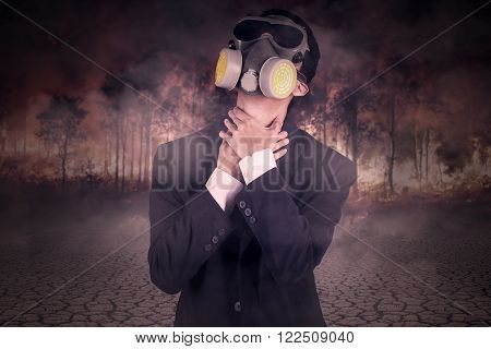 Young man in formal suit wearing a gas mask and looks chokes in the forest fire