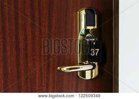 Half opened door of a room with number 37 on it. Hotel room door with lock half open. Hotel suit welcome guests. Opening door closeup. Door handle. Privacy concept. Entrance to the hotel room.