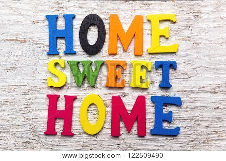 'Home Sweet Home' message wooden sign on white wooden background
