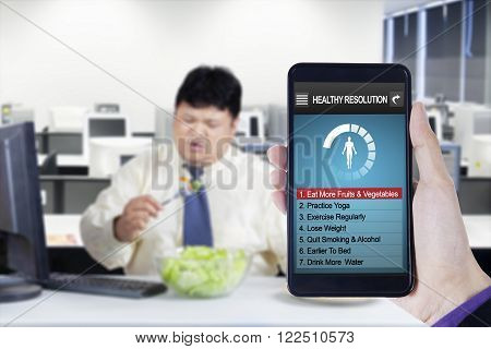 Image of hand holding smartphone with healthy resolutions program and overweight businessman eats salad in office