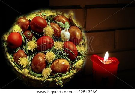 A basket of Easter eggs by the candle light in front of a brick background as a Eater Card.