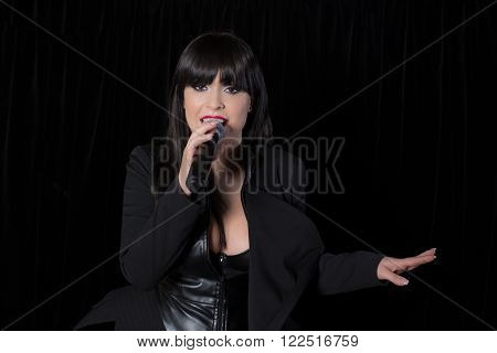 Beautiful singer singing with a microphone on stage