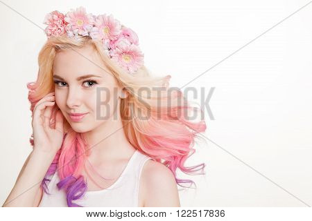 Youth women with perfect skin and colored curly hair smiling. Flowers in her hair. Studio, isolated, white background. Copyspace.