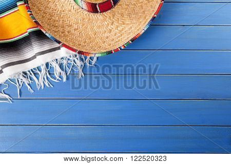 Mexican sombrero and traditional serape blanket laid on an old blue painted pine wood floor, mexico cinco de mayo festival concept
