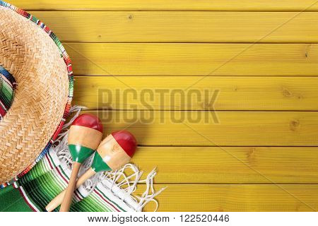 Mexican sombrero maracas and traditional serape blanket laid on a yellow painted pine wood floor. Space for copy.