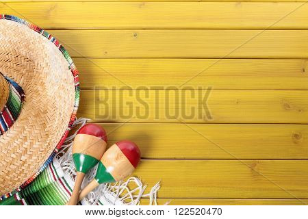Mexican sombrero maracas and traditional serape blanket laid on a yellow painted pine wood floor.