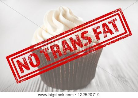 Tasty cupcake and no trans fat sign on white wooden background