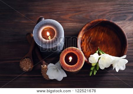 Spa composition with alight candles on wooden background