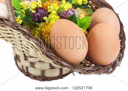 Easter eggs in brown basket with flowers