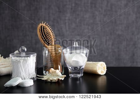 Bathroom set with wooden comb, wisp and sponges on grey background