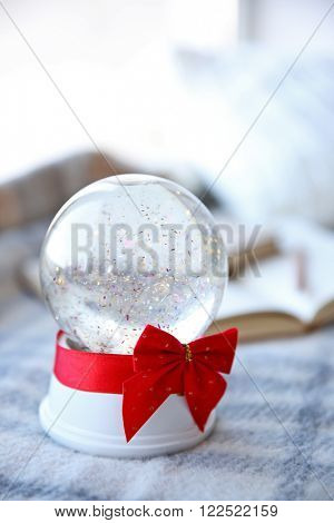 Snow globe with red bow beside the window