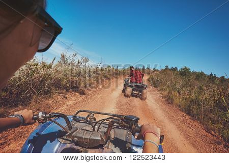 Young people driving quad bikes with man in front . Man and woman on country ride on an all terrain vehicle.