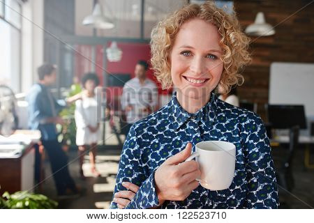 Portrait of happy young businesswoman holding a cup of coffee looking at camera and smiling. She is standing in her office with team of colleagues talking in background.
