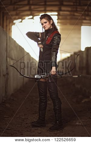 Tribal girl in leather costume with tight bowstring inside abandoned building.