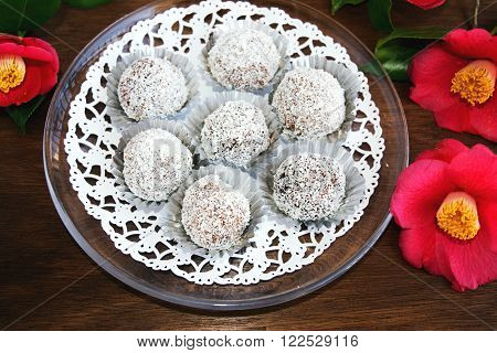 Snowball truffles of chocolate and coconut topping on wooden table with camelia. Homemade candy.
