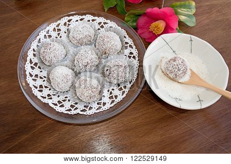 Making Snowball truffles of chocolate and coconut topping on wooden table with camelia. Homemade candy.