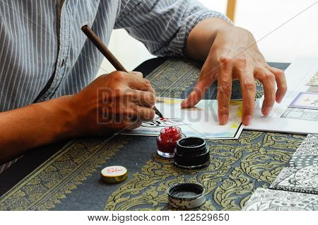 MALACCA, MALAYSIA - NOVEMBER 01, 2015: A man wrote an Arab calligraphy words on piece of paper.