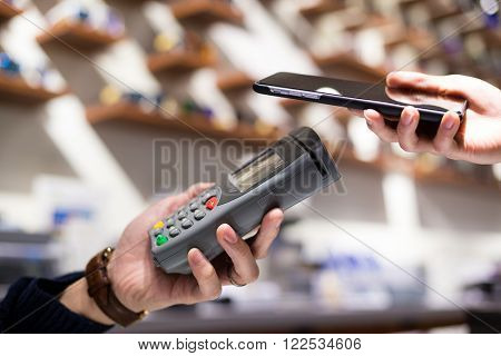 Woman using smartphont for paying the bill at shop